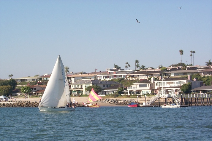 Waterfront homes with sailboat in foreground